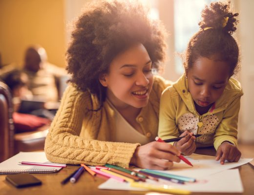 Happy African American mother assisting her daughter in coloring.