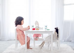 child seated at table playing with dough and dolls